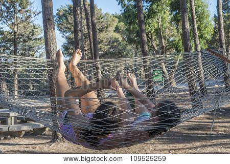 Two girls relaxing in hammock in forest showing heart sign with their hands