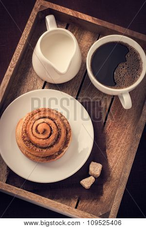 Cinnamon Roll,  Cup Of Coffee And Cream  On Wooden Tray