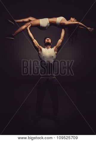 Athletic Couple Doing Acro Yoga, Studio Shot