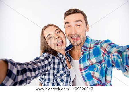 Cheerful Funny Couple In Love Making Selfie Photo Showing Tongue