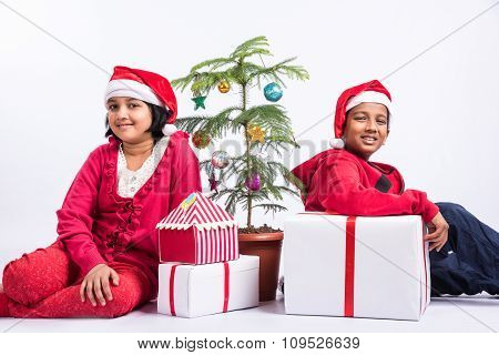 Indian girl and indian boy in red cloths and red santa hat, sitting and smiling with gift boxes and