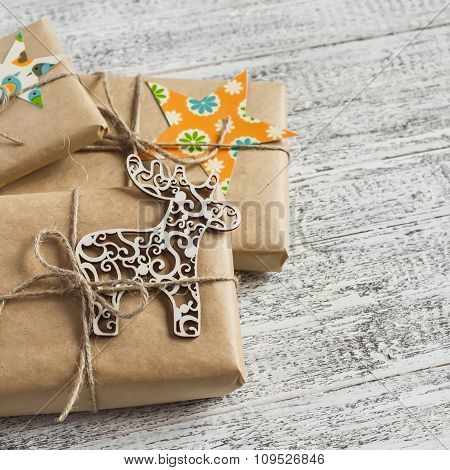 Christmas Gifts In Kraft Paper On The Bright Wooden Surface. Vintage And Rustic Style.