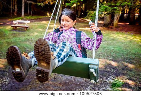 Happy Little Girl Swinging On The Swing In A Children Playground