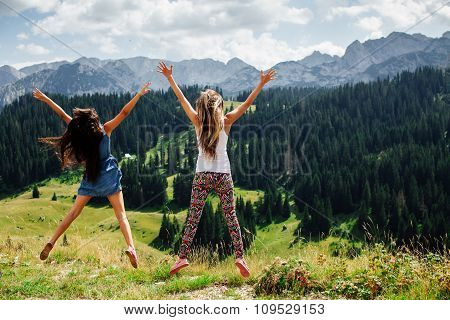 Two Girls Happy Jump In Mountains Back View