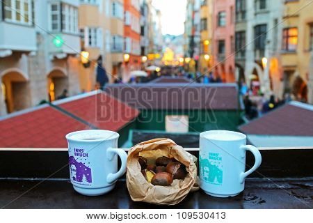 INNSBRUCK, AUSTRIA - DECEMBER 2014 : Cups of typical hot mulled gluhwein wine, Punsch and roasted chestnuts at Christmas Market in Innsbruck, Austria on December 21, 2014.