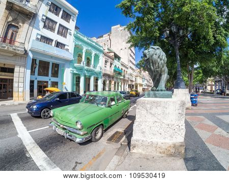 HAVANA,CUBA - NOVEMBER 12, 2015 : Street scene with old american car next to the lion at El Prado boulevard, a symbol of the city