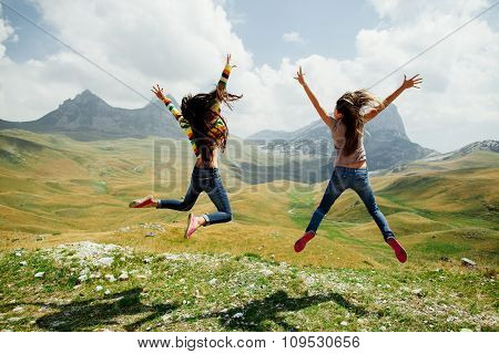 Two Girls Happy Jump In Mountains With Exciting View