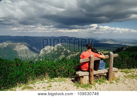 Lovely Couple Relax On Peak Of Mountains Back View