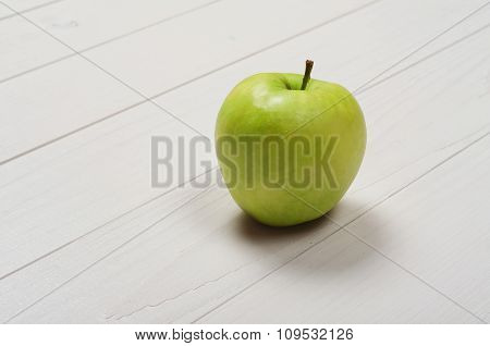 Green Ripe Apple On A White Wooden Surface