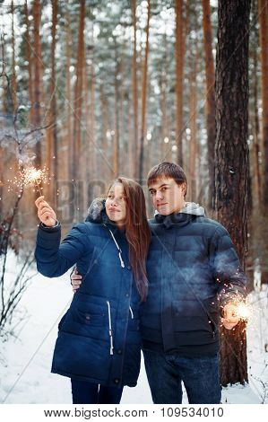 Young Family In A Winter Forest With Sparklers