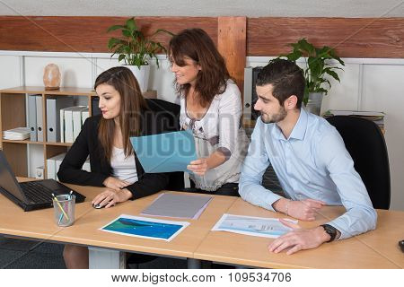 Three Colleagues Take A Break At Office Looking Document