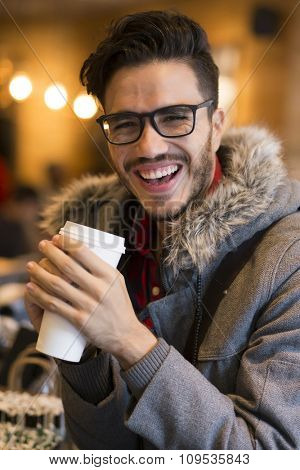 Young hipster with a tall coffee indoors in a cold day