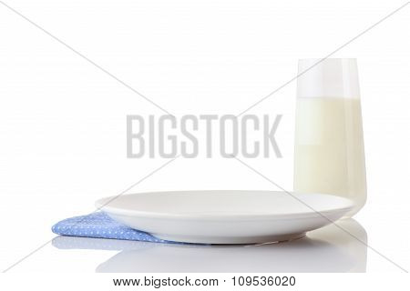 Empty white ceramic plate on blue napkin in small white polka dots and glass of milk