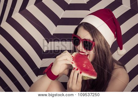 Portrait Of A Funny Smiling Girl In Santa Claus Hat And Red Sunglasses With A Slice Of Watermelon