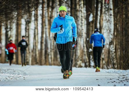 man middle-aged runner runs on road snowy Park
