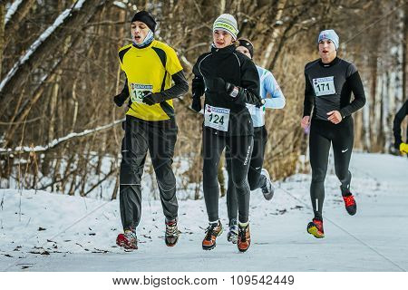 group young men and girl running through snowy trail in Park