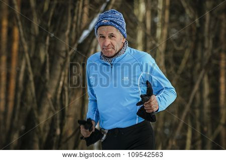 closeup face old athlete running in winter Park in cold weather