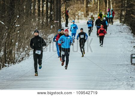 General plan running through snowy Park alley group of men athletes