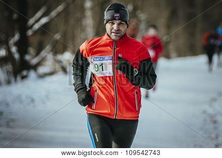 man middle-aged runner runs through snowy Park alley in December
