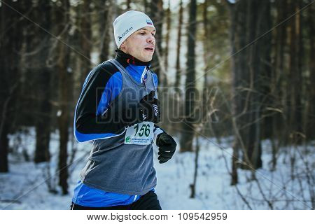 closeup of young man running in winter woods
