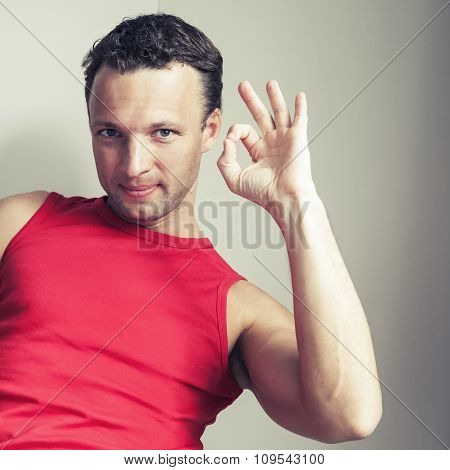 Positive Young Smiling Man Shows Okay Sign