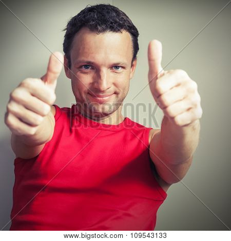 Positive Young Smiling Man Shows Thumbs Up