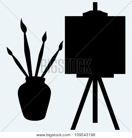 Brushes in vase and easel with empty canvas