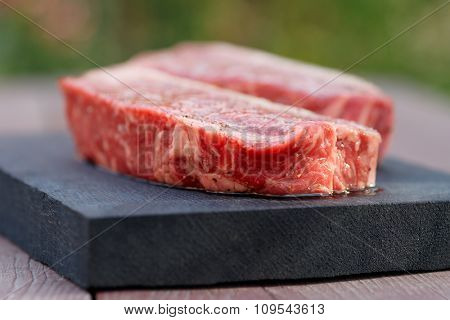 Two pieces of raw striploin steak, outdoor shot