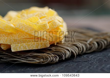 Two types of pasta on wooden plank, close-up