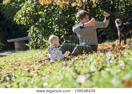 Young Father And His Toddler Child Sitting In An Autumn Grass Playing With Colourful Leaves