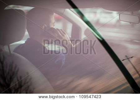 Handsome young man looking at his cellphone while at the wheel of his car, smiling