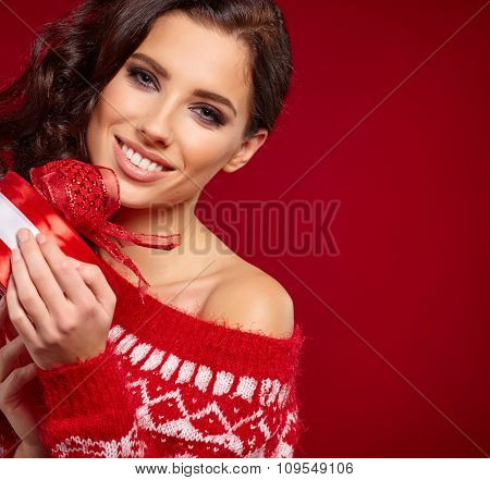 Beautiful woman portrait hold gift in christmas color style . Smiling happy girl on red background.