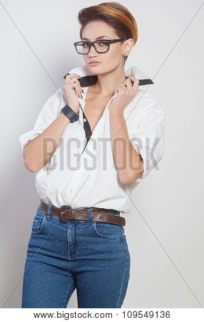 Cute young business woman with glasses and short hair, studio shoot