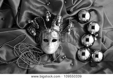 Background Of Christmas Tree Balls With Decorations And Mask On Shiny Silk Fabric With Dramatic Ligh