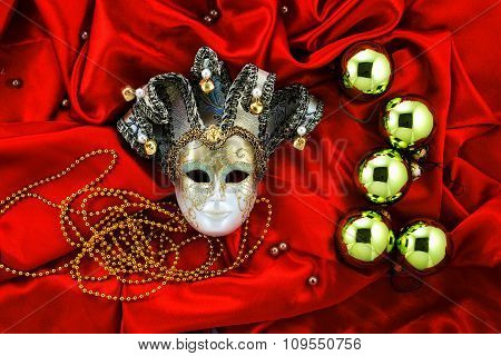 Background Of Golden Christmas Tree Balls With Gold Decorations And Golden Mask On Red Shiny Silk Fa