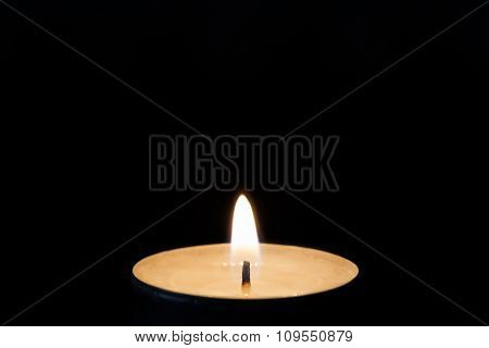 One burning tealight in darkness closeup