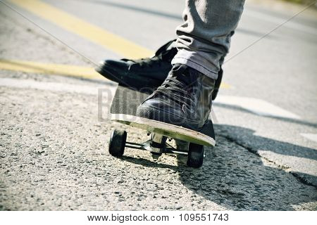 closeup of a young caucasian man skateboarding on the street, with a filter effect