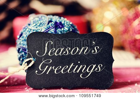 closeup of a black label with the text seasons greetings and on a rustic wooden surface with some different christmas ornaments