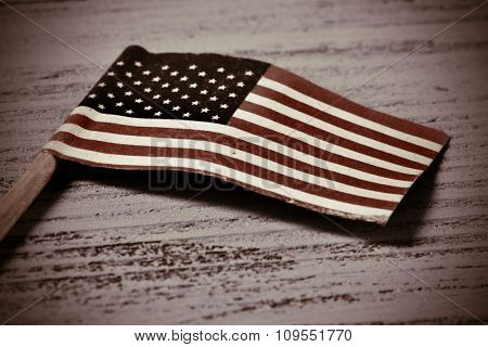 a small flag of the United States on a rustic wooden surface, with a vignette added
