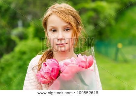Outdoor portrait of a cute little redhead girl, holding bouquet of pink peonies