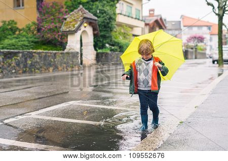Outdoor portrait of adorable little blond boy with umbrella under the rain, playing in the puddle