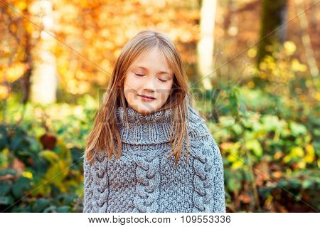 Outdoor portrait of a cute little girl in autumn forest, wearing grey knitted poncho, eyes closed