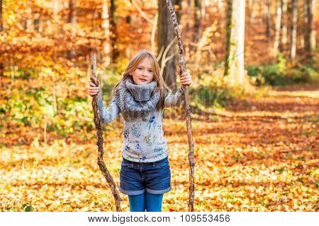 Outdoor portrait of a cute little girl in autumn forest