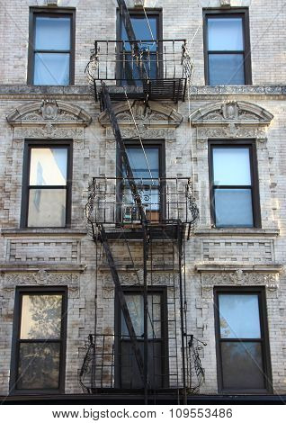 Fire Escape Steel Ladder On White Apartment Building Facade