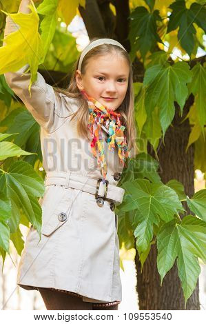Outdoor portrait of a cute little girl wearing beige trench coat
