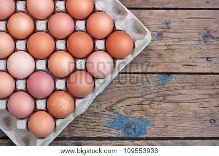 Chicken Brown Eggs In Packing On A Timber Floor, The Top View. Food, Table Still Life.