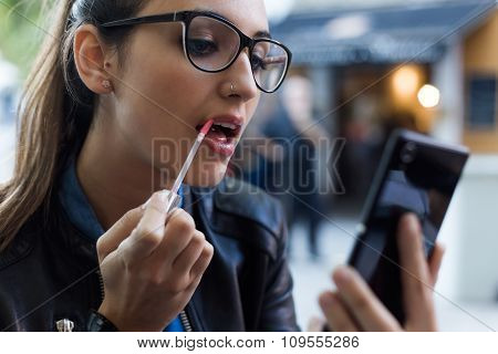 Beautiful Young Woman Making Up Using A Smart Phone As A Mirror.
