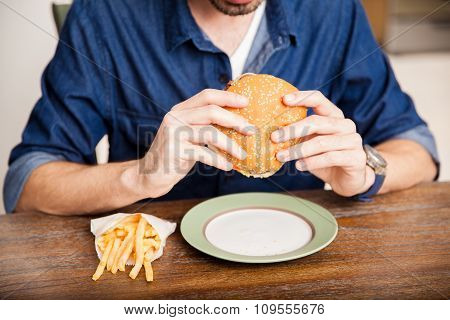 Man Eating A Burger Up Close