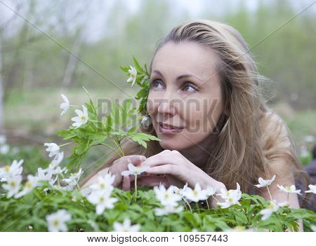 The young beautiful woman in the field of blossoming snowdrops