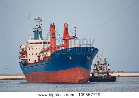 Cargo Ship And Tug Boat Maneuvering Near The Pier